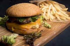 Soczysty cheeseburger z sałatą, pomidorem, cebulą, rozciekłym serem i francuzów dłoniakami, zdjęcie royalty free