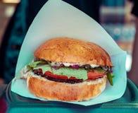 Soczysty hamburger gotujący przy grillem outdoors w rzemiosło papierze Cookout bbq ameryka?ski jedzenie Uliczny jedzenie, fast fo obrazy stock