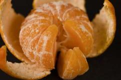 Soczysty pomarańczowy tangerine z łupą i plasterkami kłama na czarnym tle zdjęcie royalty free