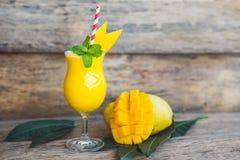 Soczysty smoothie od mango w szkle z pasiastą czerwoną słomą z nowym liściem na starym drewnianym tle i Zdrowy życia pojęcie, pol Fotografia Stock