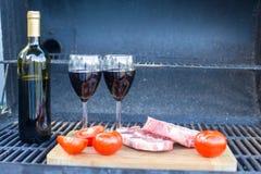 Soczysty stek, warzywa i butelka wino na pinkinie outdoors, Obraz Stock