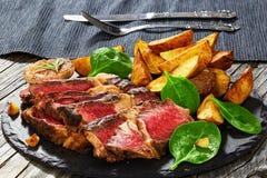 Soczysty ziobro oka wołowiny stek z smażącymi kartoflanymi klinami Zdjęcie Royalty Free