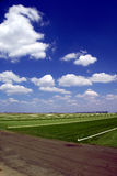 Sod Farming. Green Grass Sod Farmland under Puffy White Summer Clouds and Deep Blue Sky stock images