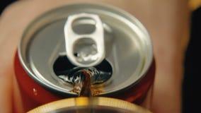 A soda é derramada de uma lata da cor vermelha contra um fundo escuro tiro do close-up do Lento-movimento filme