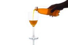 Soda anaranjada que vierte en el vidrio Fotografía de archivo