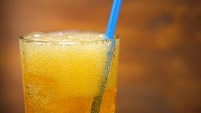 Soda anaranjada que vierte en el vidrio con el cubo de hielo almacen de metraje de vídeo