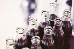 Soda de refrescamento de Brown em umas garrafas na barra de chocolate na tabela Imagem de Stock Royalty Free
