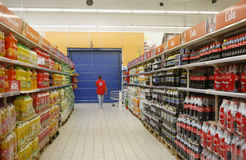 Soda department in supermarket. An employee is passing by the soda department in the aisle inside a department store