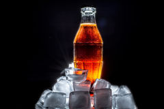 Soda glass bottle in ice cube with beautiful reflection and patches of sunlight on black Royalty Free Stock Photos