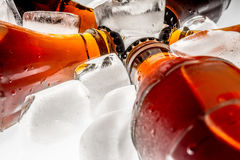 Soda glass bottles in a refrigerated ice cubes on light background Royalty Free Stock Image