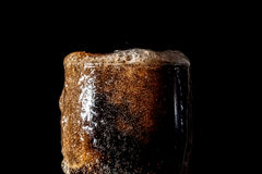 Soda large glass, overflowing glass of soda closeup with bubbles isolated on black Royalty Free Stock Photo