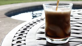 Soda pouring into a glass with a pool in the background. stock video footage