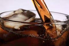 Soda que vierte sobre el hielo Foto de archivo