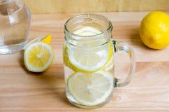 Sodavatten med citronen i krus på trätabellen - citronsodavatten arkivbild