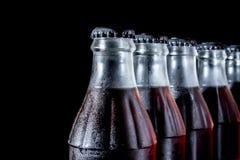 Sodavattenglasflaskor som i rad står isolerade på en svart Royaltyfri Bild