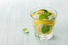 Sodawasser oder Mineralwasser mit Kalken, Zitronen, Eis und tadellosen Blättern auf hellblauem Hintergrund Stockbild