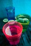 Sodawater, soda of een jenever en een tonicum in kleurrijke glazen met citroen en ijs Royalty-vrije Stock Foto's