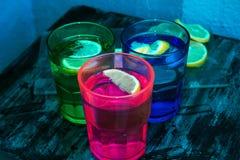 Sodawater, soda of een jenever en een tonicum in kleurrijke glazen met citroen en ijs Stock Fotografie