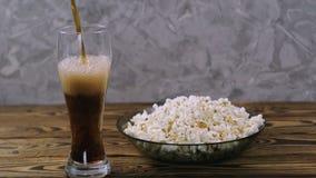 Sodawater in transparant glas dichtbij volledige kom popcorn wordt gegoten die stock footage
