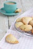 Słodcy mali kulebiaki i filiżanka kawy z mlekiem na podławym drewnianym t Zdjęcie Royalty Free