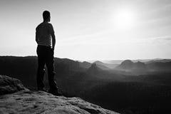 Soddisfaccia la viandante alta in camicia grigia e pantaloni scuri Sprtsman sul picco del bordo tagliente della roccia che guarda Fotografia Stock