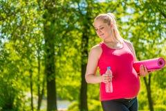 Soddisfatto con la donna incinta che tiene una stuoia di yoga Immagini Stock
