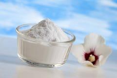 Sodium dwuwęglan w szklanym słoju z kwiatem na błękitnym tle fotografia royalty free