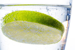 Sodium silicate and lime. A glass of fresh drinking water and a lime. mineral water as a thirst quencher Stock Photography