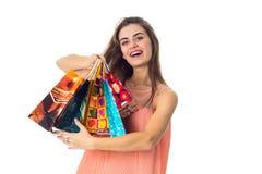 Słodka dziewczyna utrzymuje pakunki z zakupami w ręce i śmia się Zdjęcie Royalty Free