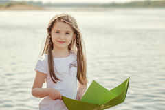 Słodka mała dziewczynka pozuje z papierową łodzią, zakończenie Zdjęcia Stock