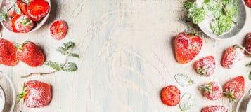 Słodkie truskawki z sproszkowanym cukierem i nowymi liśćmi na białym podławym modnym drewnianym tle Obrazy Royalty Free