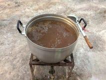 Soep in een grote pot op het fornuis en lepel naast royalty-vrije stock afbeeldingen