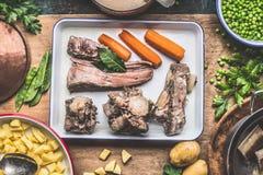 Soep kokende voorbereiding met gekookt vlees, groenten, aardappels en groene erwten op rustieke keukenlijst stock foto