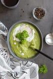 Soep met broccoli en room en lepel op grijze achtergrond stock foto