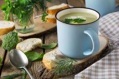 Soep van broccoli en avocado keramtcheskoy blauwe kop op de oude houten lijstachtergrond Royalty-vrije Stock Fotografie