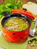 Soep van groene erwten met vlees in rood kom en brood aan boord Royalty-vrije Stock Fotografie