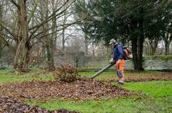 Soest, Duitsland - December 18, 2017: De mens met stofzuiger maakt het park van de bladeren schoon stock foto's