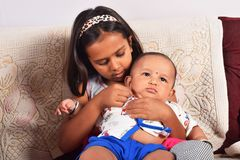 Soeur étreignant le frère heureux de bébé s'asseyant sur le sofa, Pune, maharashtra image stock