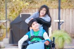 Soeur adolescente prenant soin de frère handicapé dans le fauteuil roulant  Photographie stock