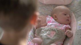 Soeur de apaisement de bébé de frère aîné à dormir dans la chaise de basculage banque de vidéos