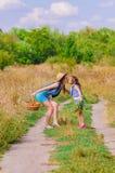 Soeur de filles dans un domaine avec des fleurs Photographie stock