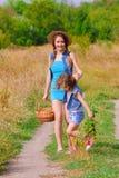 Soeur de filles dans un domaine avec des fleurs Image stock