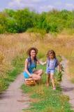 Soeur de filles dans un domaine avec des fleurs Photographie stock libre de droits