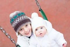 Soeur de frère et de bébé balançant en parc Photo stock