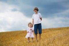 Soeur de frère et de bébé marchant dans un domaine de blé d'or Image libre de droits