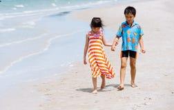 Soeur de frère tenant la promenade de main sur la plage Images stock