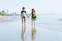 Soeur de frère tenant la promenade de main sur la plage Photo libre de droits