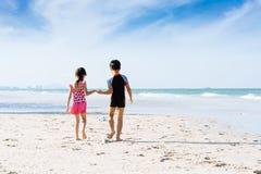 Soeur de frère tenant la promenade de main sur la plage dans la bouteille de colleact Photo libre de droits