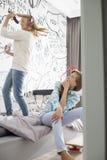 Soeur de observation de fille chantant dans la brosse à cheveux dans la chambre à coucher Image libre de droits