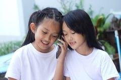 Soeur deux heureuse avec un téléphone portable Images libres de droits